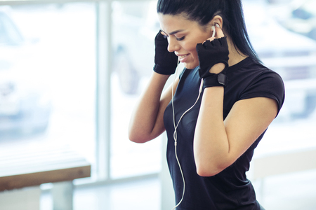 woman is going to listen music, wearing earphones and lokking focused Stock Photo