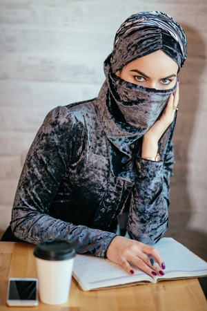 muslim Woman writing on her notebook in cafe