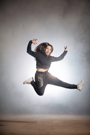 woman in black clothers is trying to do the spilts in the air Stock Photo
