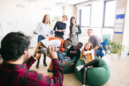 stylish young diverse students are posing to the camera for journalist Foto de archivo