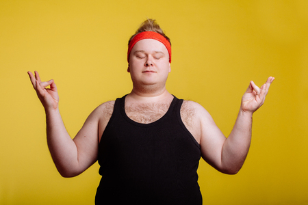 fat man relaxing with meditation on yellow background Zdjęcie Seryjne