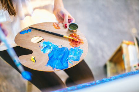 Woman artist mixing oil colours on palette holding in her hand