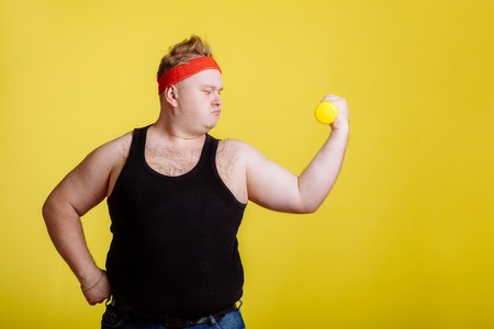 fat man with dumbbell on yellow background. Motivation for fat people Stock Photo