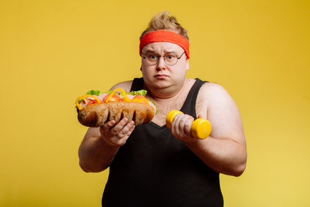 Fat man choise between sport and fastfood