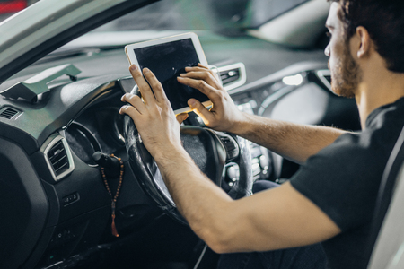 Mechanic Sitting In Car Looking At Digital Tablet in garage