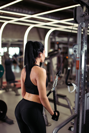 rear view fit woman execute exercise with exercise-machine Cable Crossover in gym