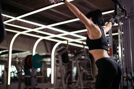 woman exercising power cable crossover for chest muscles at gym