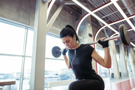 girl doing lunges with barbell in modern gym