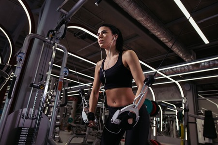 fit woman execute exercise with exercise-machine Cable Crossover in gym
