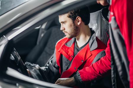 Mechanik bada silnik samochodu przy pomocy laptopa Zdjęcie Seryjne