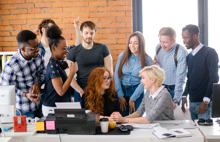 cheerful businesspeople congratulating their red-haired co-worker with career development