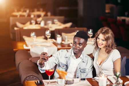 Attractive mixed-race couple taking selfie at the restaurant