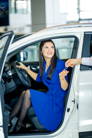 Young smiling woman sitting in car receiving key. Rent, purchase, selling