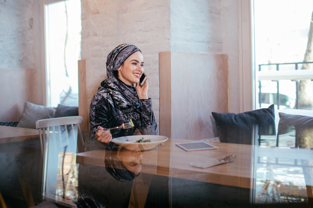 young muslim woman talking on phone in cafe and looking on window Banque d'images