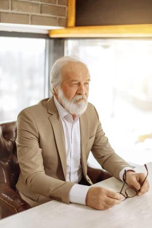 old handsome businessman in smart clothers making plans.