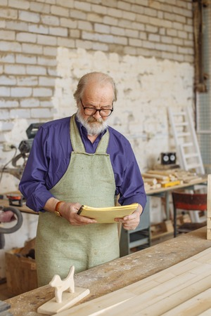 old man wearing blue shirt and apron is looking at the exercise book