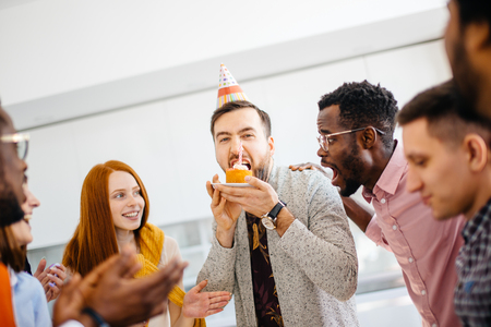 greedy guy is trying to bite a bigger peace of cake in front of friends