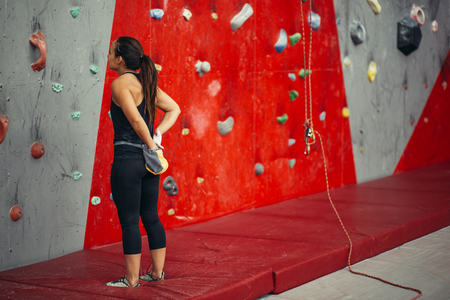 Rear view of sportswoman looking at climbing wall