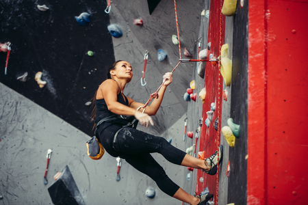 Active happy woman overhanging on tightrope in the training climbing center