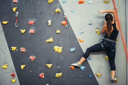 Sporty young woman training in a colorful climbing gym.