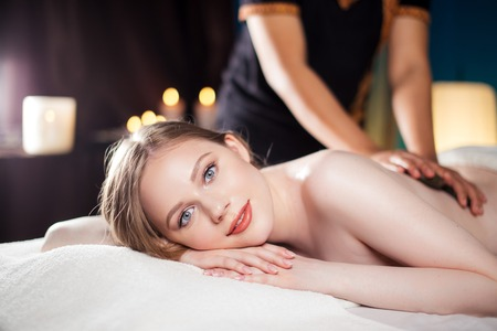 Beautiful, young and healthy woman is having hot stone massage. Spa Treatment Stock Photo