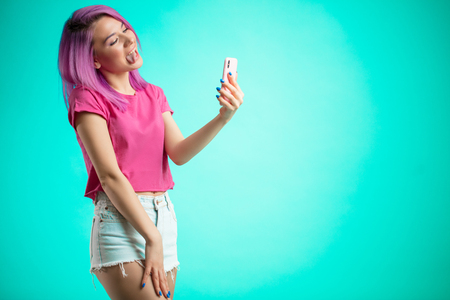 smiling woman making selfie photo on smartphone isolated on a blue background