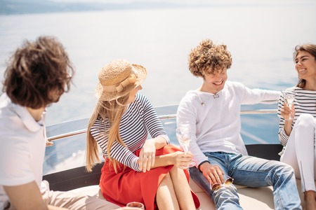Friends having fun sailing on a yacht in sea, laughing, chatting and chilling Stock Photo