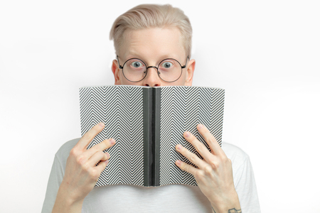 Surprised blond man covering their mouth with opened grey over white background Stock Photo