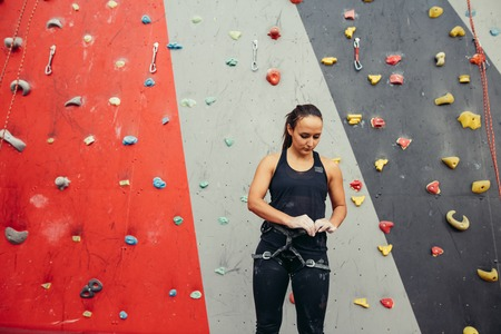 trainer typing harness of woman on climbing wall in gym Banco de Imagens