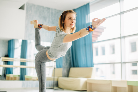 Young fit woman doing a yoga pose standing with one leg raised up. 版權商用圖片