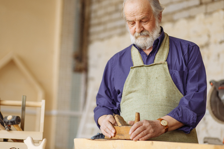 old experienced carpenter working with wooden planer on plank workshop.