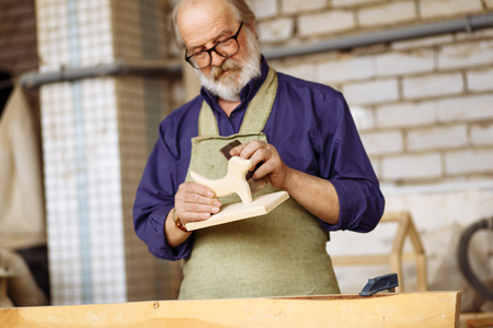 senior citizen is making wood toy smoother with sandpaper