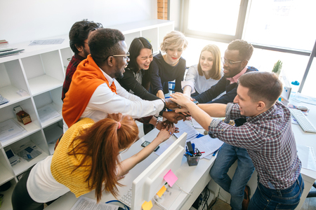 Creative happy multinational business team putting hands together at the office Stock Photo