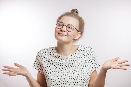 Portrait of a beautiful model shrugging shoulders isolated on a white background