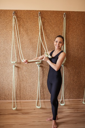 young beautiful fitness girl holding the ropes in the modern gym