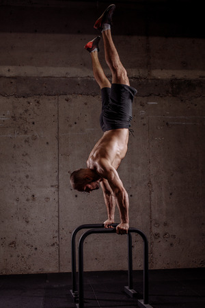 young ambitious sporty man performing hand stand on P bars