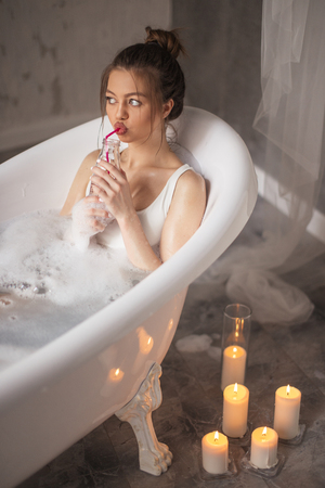 Beautiful woman sits in tube in hydrotherapy spa and drink cocktail