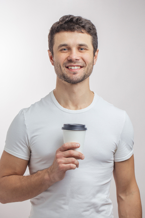 close up portrait. a happy handsome man with paper cup of morning coffee 版權商用圖片