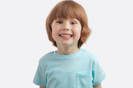 pretty red-haired kid showing his white teeth Standard-Bild