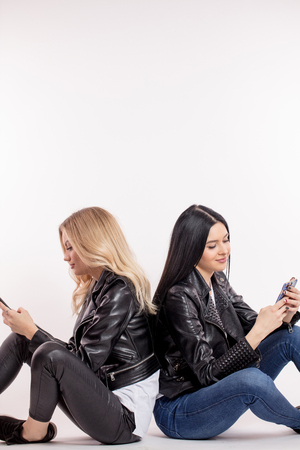 two gorgeous women ignoring each other, surfing the net