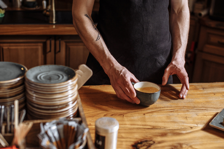 Mann hält eine Tasse mit Kaffeesatz