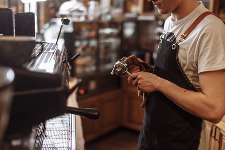 a waiter is drying the coffee grinder after washing