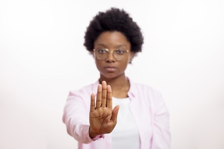 serious afro woman in glasses making stop gesture. Don't smoke. stop talking, keep silence. pay attention , note, warning concepts. focus on the palm. blurred background. hypnosis