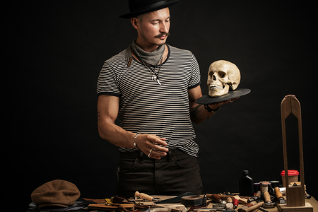 Stylish man with mustache wearing hat and holding scull posing indoors Zdjęcie Seryjne