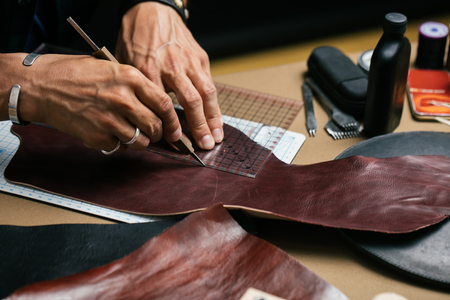 Close up of skinner craftsman working with natural leather using craft tools.