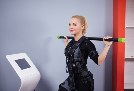 awesome sporty woman in EMS costume and stick is posing to the camera