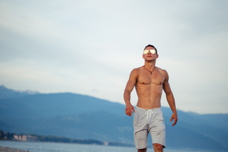 Masculine body man in sunglasses at beach with mountauns on background Stock Photo