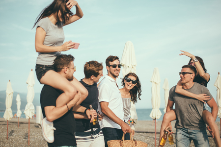 Group of Friends Walking at Beach, having fun, womans piggyback on mans, funny vacation Banco de Imagens
