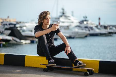 hipster man sitting on longboard using his phone 版權商用圖片