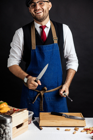 Midsection of male chef sharpening knife in commercial kitchen